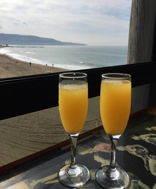 two champagne glasses with Mimosas