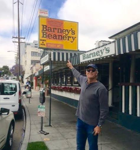 Doug Mcintyre pointing at Barney's Beanery sign